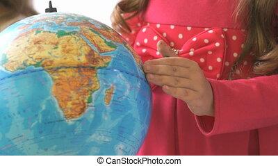 Little girl rotates the globe of world