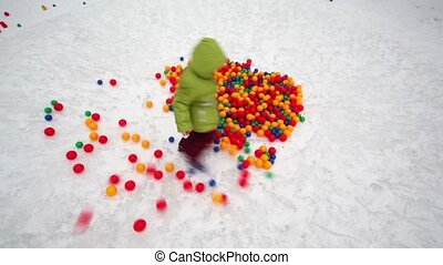 Little girl run around pile of colored balls at winter