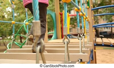 Little girl run on hang down wooden steps at playground