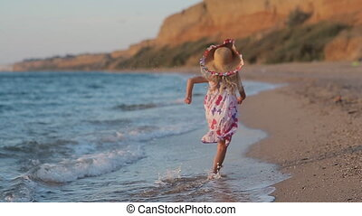 Little blond girl runing along the beach in sundress in slow motion back view