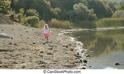 Little girl runing along the shore of lake in slow motion