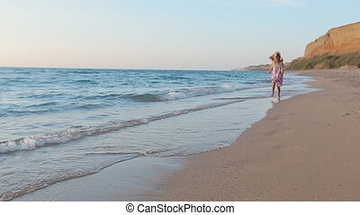 Little girl running along the sea to father leaving footprints on the sand and he lifts her up in slow motion