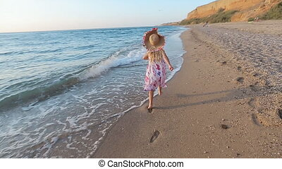 Little girl running along the sea to her parents leaving footprints on the sand