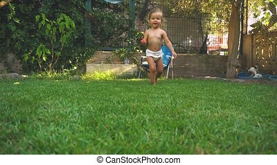 Little girl running and laughting on lawn in summer day at...