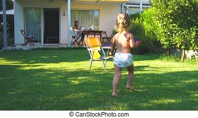 Little girl running and sitting down at chair at backyard in...