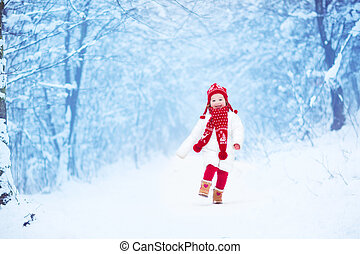 Little girl running in a snowy park - Happy laughing toddler...