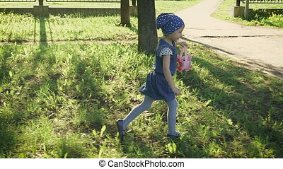 Little girl running in the park. It accelerates urban pigeons, for her fun.