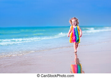 Little girl running on a beach - Happy laughing little girl...