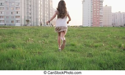 Little girl running on grass on urban wasteland
