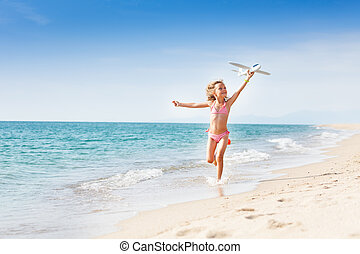 Little girl running on the coast with toy plane