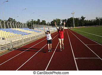 Little girl running on the stadium with a coach