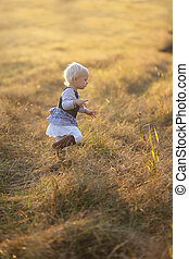 Little Girl Running Through Golden Field at Sunset