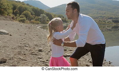 Little girl running to father and he turns her in slow motion