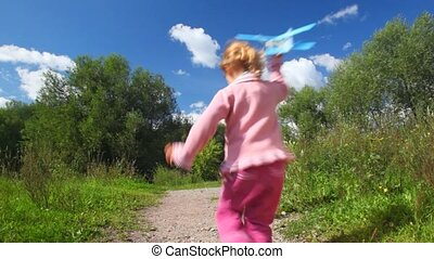 little girl running with toy aircraft, from camera