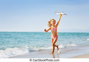 Little girl running with toy plane on the beach