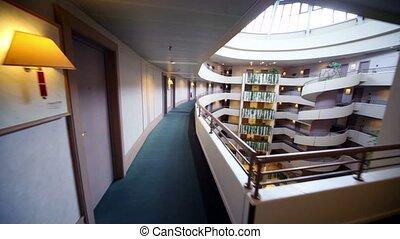 Little girl runs along balcony at top level of multiple floor building