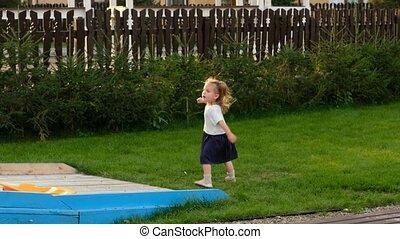 Little girl runs down slide and returns up on playground
