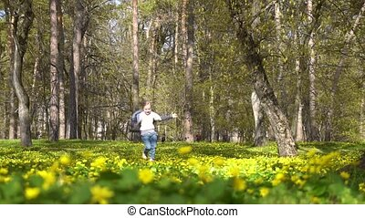 little girl runs in the spring blossoming forest