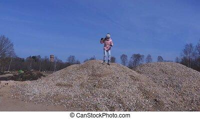 Little girl runs over gravel piles