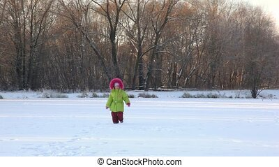 little girl runs to camera in wintry park - little smiling...
