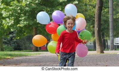 little girl runs with multicolored balloons, Summertime. Slow motion. Close up