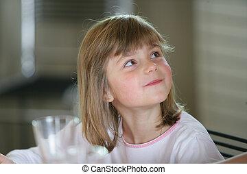Little girl sat at kitchen table