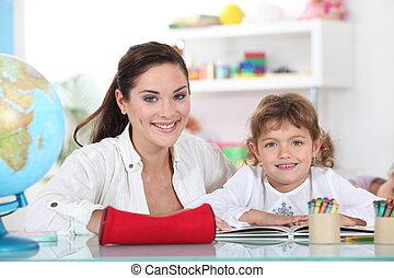 Little girl sat with teacher in class room