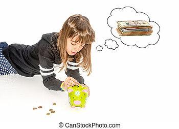 Little girl saving money in piggy bank