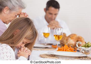 Little girl saying grace with family before thanksgiving dinner