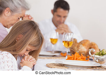 Little girl saying grace with family before thanksgiving...