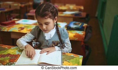 little girl schoolgirl sitting at her desk teaches lessons lesson. the beginning of the school year. girl lifestyle in school concept