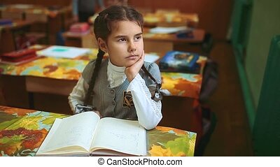 little girl schoolgirl sitting at her desk teaches lessons lesson. the beginning of the school year. girl in lifestyle school concept