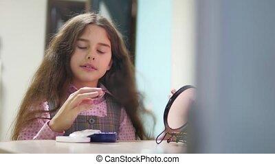little girl schoolgirl smears face cream. face care girl...