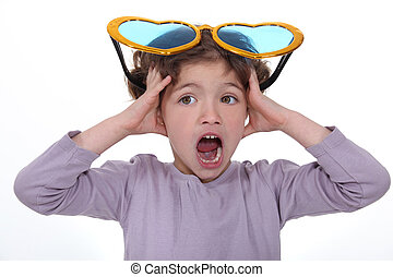 Little girl screaming with huge funny sunglasses on head