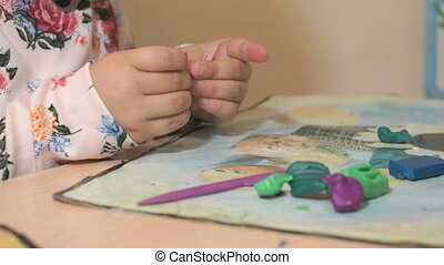 Little girl sculpting figures from plasticine - Unknown...
