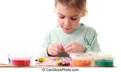 Little girl sculpts plate of plasticine sitting at table -...