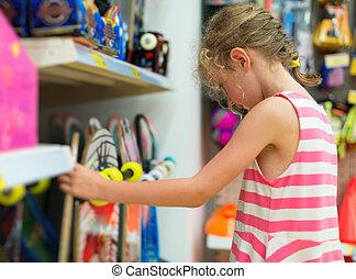 Little girl selecting skateboard in supermarket.
