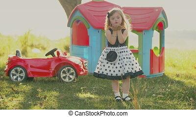 little girl sends an air kiss - little girl in nature blows...