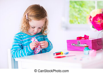Little girl sewing a dress for her doll