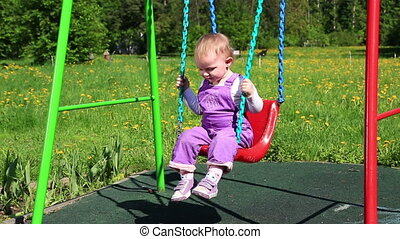 little girl shakes on a swing at a playground