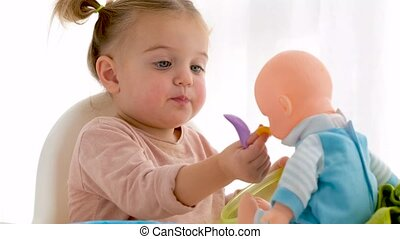 Funny little girl puffing cheeks and giving cereals to baby doll while having breakfast at home in morning