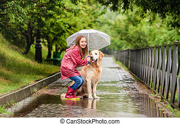 Little girl sharing umbrella with dog