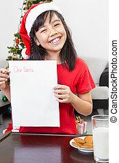 Little girl showing blank letter to Santa