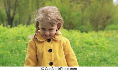 Little girl showing dandelion on a camera. Slowly