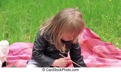 Little girl showing decorative egg and smiling on a lawn in a park. Slowly