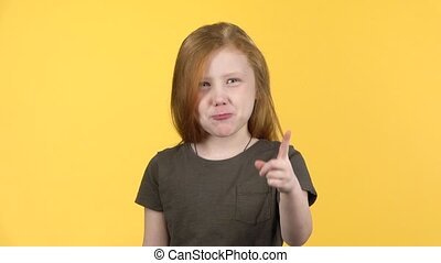 Little girl showing emotion punishment, compositing on yellow background. Slow motion