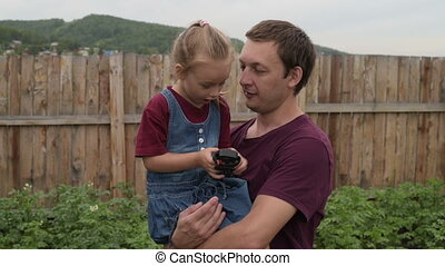 Little girl showing her dad a strange toy. Both are happy....