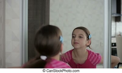 Little girl shows faces in front of a mirror