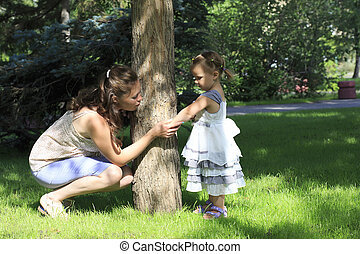 Little girl shows her mother insect bite (in a city park).