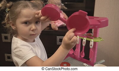 little girl shows her toys utensils in the toy kitchen